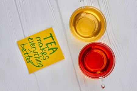 Two cups of black and green natural tea. Glass cups of aromatic tea on wooden background, top view. TEA makes everything better.