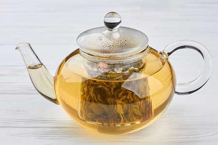 Teekanne aus Glas mit grünem Tee. Transparente Teekanne aus Glas auf weißem Hintergrund aus Holz. Standard-Bild