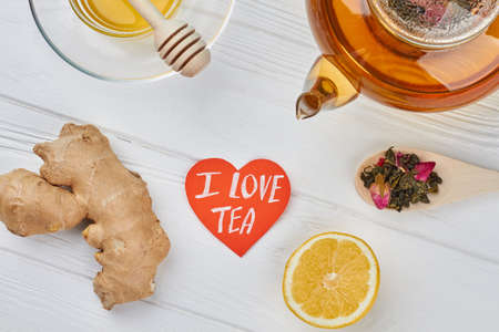 I love TEA concept. Teapot, honey, lemon, ginger root, spoon with dry tea and heart-shaped paper card. Ingredients for aromatic drink.