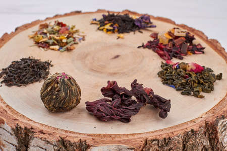 Different types of dry tea on tree slice. Assortment of dried tea leaves on natural wood.