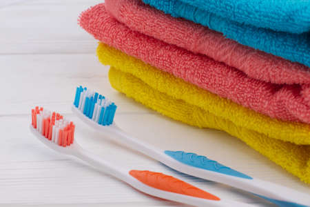 Two toothbrush and stack of colorful towels. Bath towels and toothbrush on white background. Personal hygiene, daily routine and body care toiletries concept.