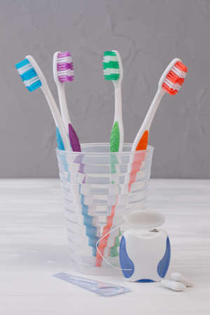 Toothbrush in glass, dental floss and chewing gums. Dentistry and health care concept.