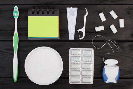 Dental cleaning tools on black background. Toothbrush, dental floss toothpick, chewing gums and blank paper notebook.