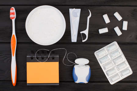 Set of dental hygiene tools on black background. Toothbrush, powder for cleaning teeth, dental floss, chewing gums and blank spiral notepad. 写真素材