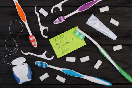 Dentist appointment message and tooth care products. Dentist appointment card, toothbrush, dental floss and chewing gums on black background. 写真素材