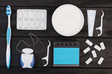 Dental health concept. Toothbrush, dental floss, cleaning powder and blank planner on woden background. 写真素材
