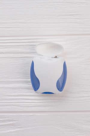 Dental floss on white wooden background. Hygienic dental floss. Dental care concept.