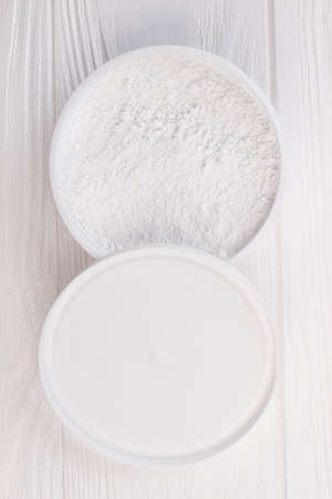 Powder for teeth cleaning, top view. Jar with powder for teeth cleaning on white wooden background. Reklamní fotografie