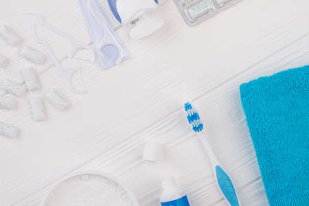 Dental hygiene tools on white wooden background. Dental care products and copy space. Teeth cleaning at home.
