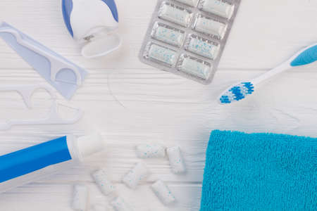 Toothpaste, toothbrush, dental floss and towel. Flat lay composition with toothbrush and oral hygiene products on wooden background. Dental health concept.