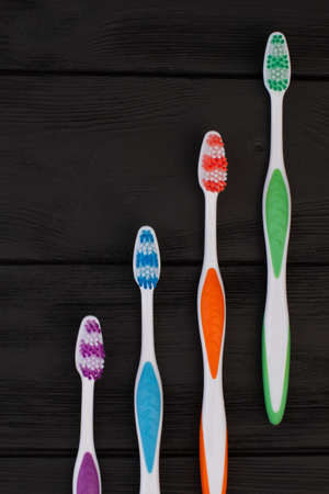 Group of tooth brushes on black wooden table. Set of multicolored tooth brushes. Space for text. Reklamní fotografie