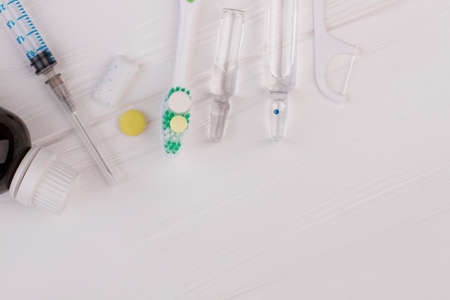 Toothbrush, ampoules with medicine and syringe. Dental care accessories on the white wooden background with copy space.