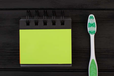 Blank binder notebook and toothbrush. Green spiral notepad and tooth brush on black background. Flat lay composition.