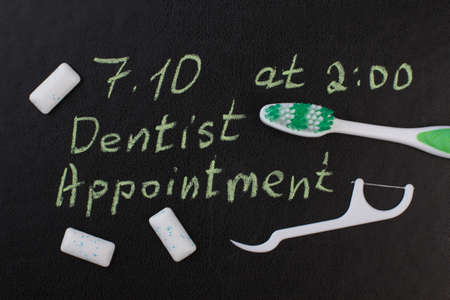 Toothbrush, dental floss and inscription dental appointment. Marked date and toothbrush to remind dentist appointment day in october. Reklamní fotografie