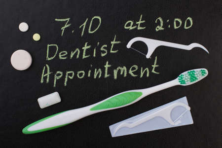 Oral care products on black background. Dental care accessories to remind dentist appointment day.