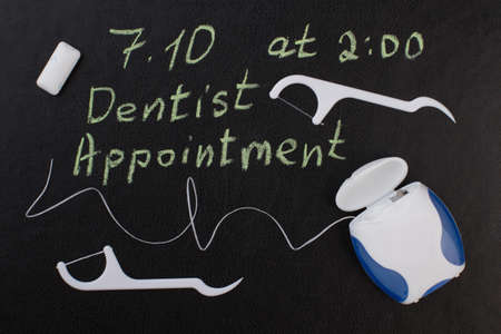 Note dentist appointment and dental floss. Reminder dentist appointment on chalkboard and dental care products. Reklamní fotografie