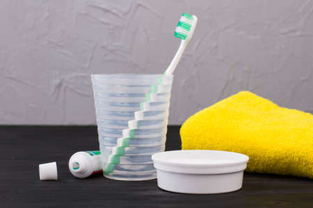 Toothbrush in glass, toothpaste and towel in bathroom. Equipment for oral hygiene. Dental health concept.
