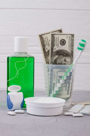 Dental hygiene tools and money. Oral care products set and American dollars on wooden background.