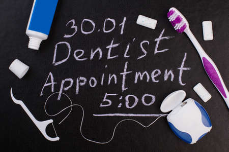 Dental care accessories and dentist appointment inscription. Dentist appointment reminder and oral hygiene products on chalkboard.