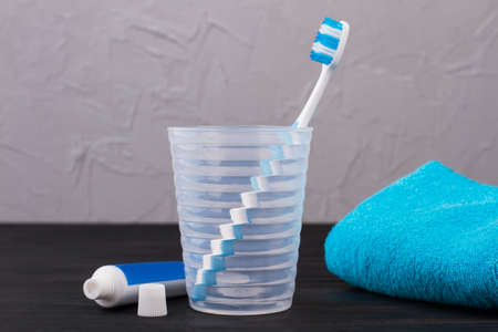 Glass with toothbrush, toothpaste and towel. Toothbrush in plastic glass, toothpaste and towel. Cleaning teeth at home.