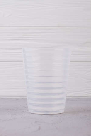 Empty plastic glass on white wooden background. Transparent plastic glass on wooden table. 스톡 콘텐츠