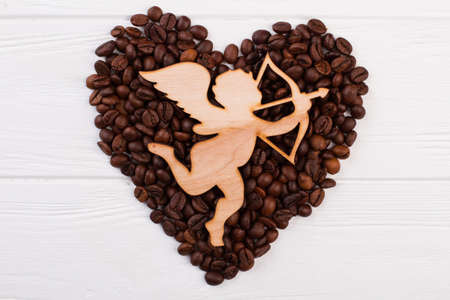 Roasted coffee beans in a shape of heart and wooden cupid. Cupid figure with arrow and shape of heart from coffee beans on white background.