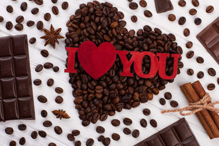 Heart shaped coffee beans and inscription I love you. Creative composition with coffee and chocolate for Valentines Day.