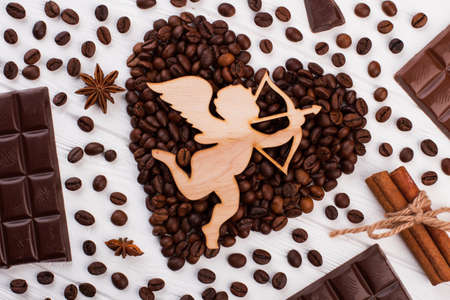 Heart shaped coffee beans and cupid with arrow. Happy Valentines Day background. Romantic composition for beloved.