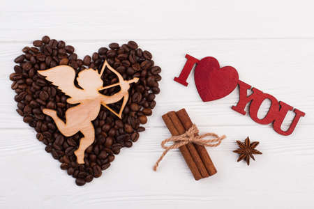 Romantic composition with coffee beans. Heart from coffee beans, wooden cupid with arrow and inscription I love you. Love and romance. Stock fotó