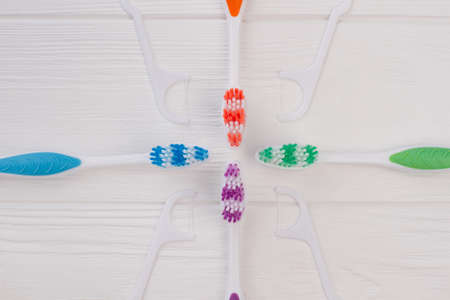 Composition with tooth brushes and dental floss. Four colorful toothbrushes and white dental floss picks. Concept of dental care. 写真素材 - 129552789