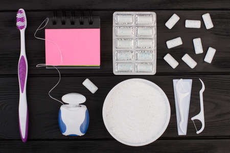 Dental care items on black background. Toothbrush, dental floss, teeth cleaning powder and spiral notepad. Dental health concept. 写真素材