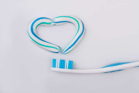 Toothbrush and toothpaste in the shape of a heart. Love healthy teeth concept.