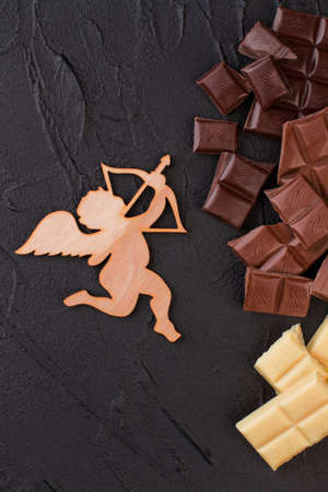 Wooden figure of cupid and chocolate pieces. Romantic background with plywood amour and various pieces of chocolate, top view.