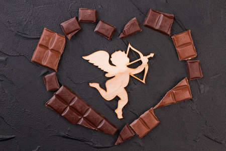Heart made of chocolate and wooden cupid. Valentines Day background with chocolate pieces and wooden cupid with arrow.