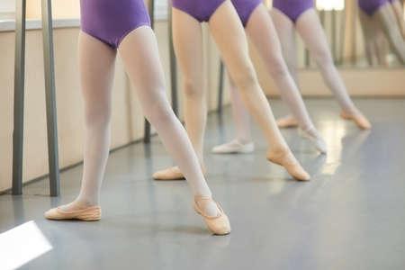 Piernas de jóvenes bailarinas en clase de ballet. Bailarines de ballet en posición de baile cerca de la barra, se centran en la primera chica. Foto de archivo