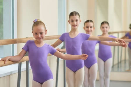 Young ballerinas standing near ballet barre. Group of young ballet dancers in purple leotards at the ballet barre. Lesson of ballet dance. Stockfoto