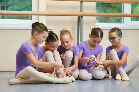 Cute little ballet dancers sitting on floor. Five beautiful ballerinas sitting on the floor and looking at new ballet shoes. Friendship and reliability. Foto de archivo - 129948990
