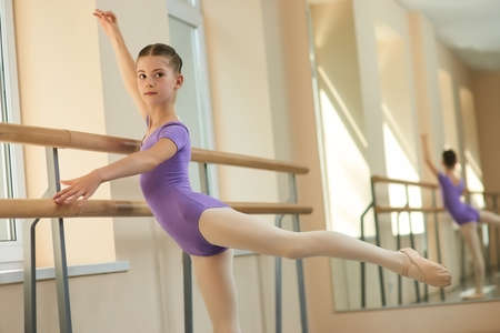Young ballerina doing exercises. Young girl stretching out near railing at classical ballet dance hall. Skillful and talented ballet-dancer.