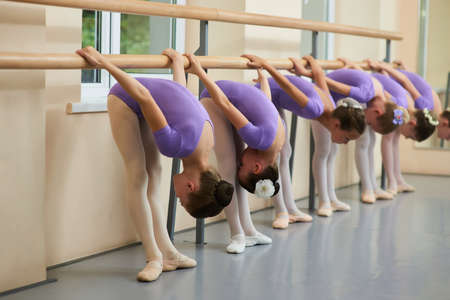 Young ballerinas performing flexibility exercises. Group of young ballet dancers bent down at ballet barre in ballet dance hall.