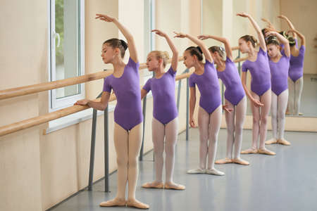 Kids rehearsing at ballet dance school. Group of girls practicing ballet at ballet barre. Childrens ballet school.