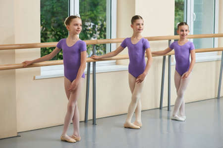 Beautiful young ballerinas with crossed legs. Three young ballet girls standing at ballet barre during lesson. Pretty ballet dancers at classical ballet classes.