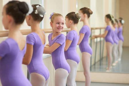 Little ballet performers practicing in studio. Young smiling ballerina looking aside. Children workouts at ballet studio.