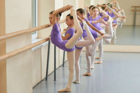 Young ballerinas doing exercises in studio. Young ballet actresses training dance move at ballet barre in dance class. Flexibility and skills of young ballerinas bodies.