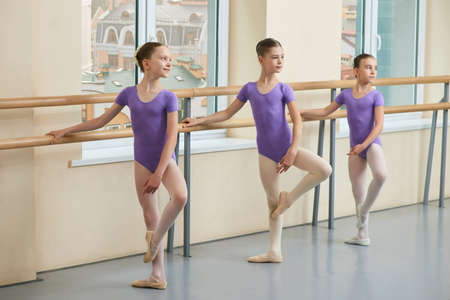 Cute ballerinas on window city background. Young ballet girls practicing ballet at ballet barre in dance studio. Tender ballet girls in purple leotard.