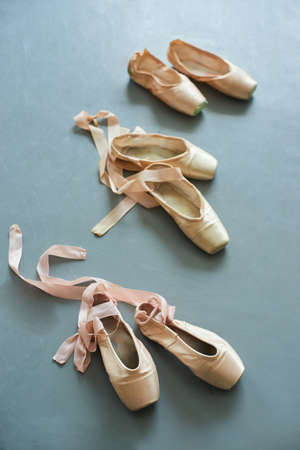 Pink pointe shoes with satin ribbon. Ballerinas footwear for training on grey background. Three pairs of slippers for ballet dance. Foto de archivo