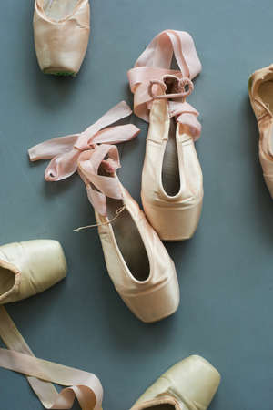 Pointe shoes with pink silk ribbon. Old used ballet slippers on the floor.