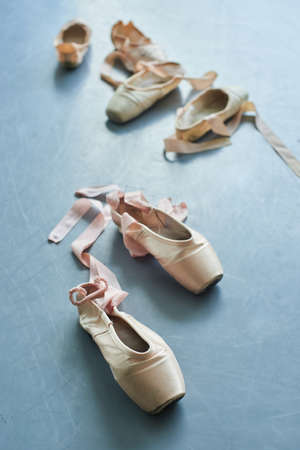 Pair of old ballet shoes on grey background. Ballerinas used pointe shoes with satin ribbon. Ballet slippers still life.