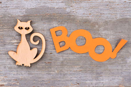 Halloween holiday decorations on wooden background. Wooden silhouette of cat and word boo on wooden surface.