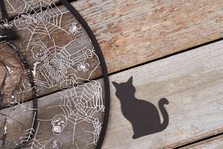 Witch hat and silhouette of cat cut from paper. Halloween party accessories on a rustic wooden background. Halloween holiday theme.
