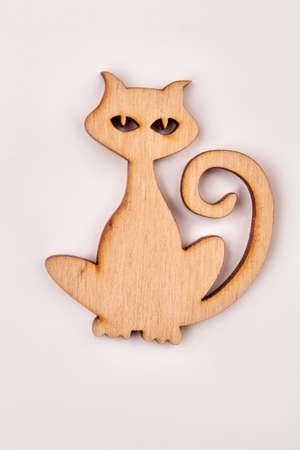 Wooden silhouette of a cat, vertical image. Plywood animal cutout isolated on white background. Decorative pet cut from wood.
